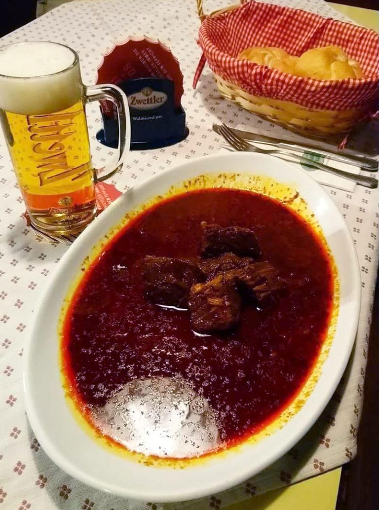 Gulasch mit Glas Bier am Tisch